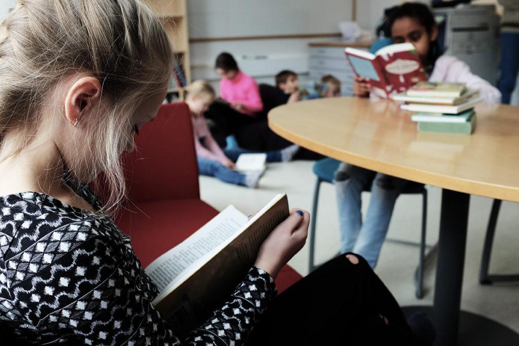 Kaksi tyttöä lukee kirjoja pöydän ääressä taustalla neljä lasta istuu lattialla lukemassa.