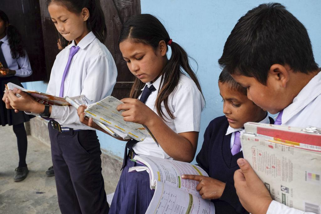 4 lasta seisoo ja lukee.